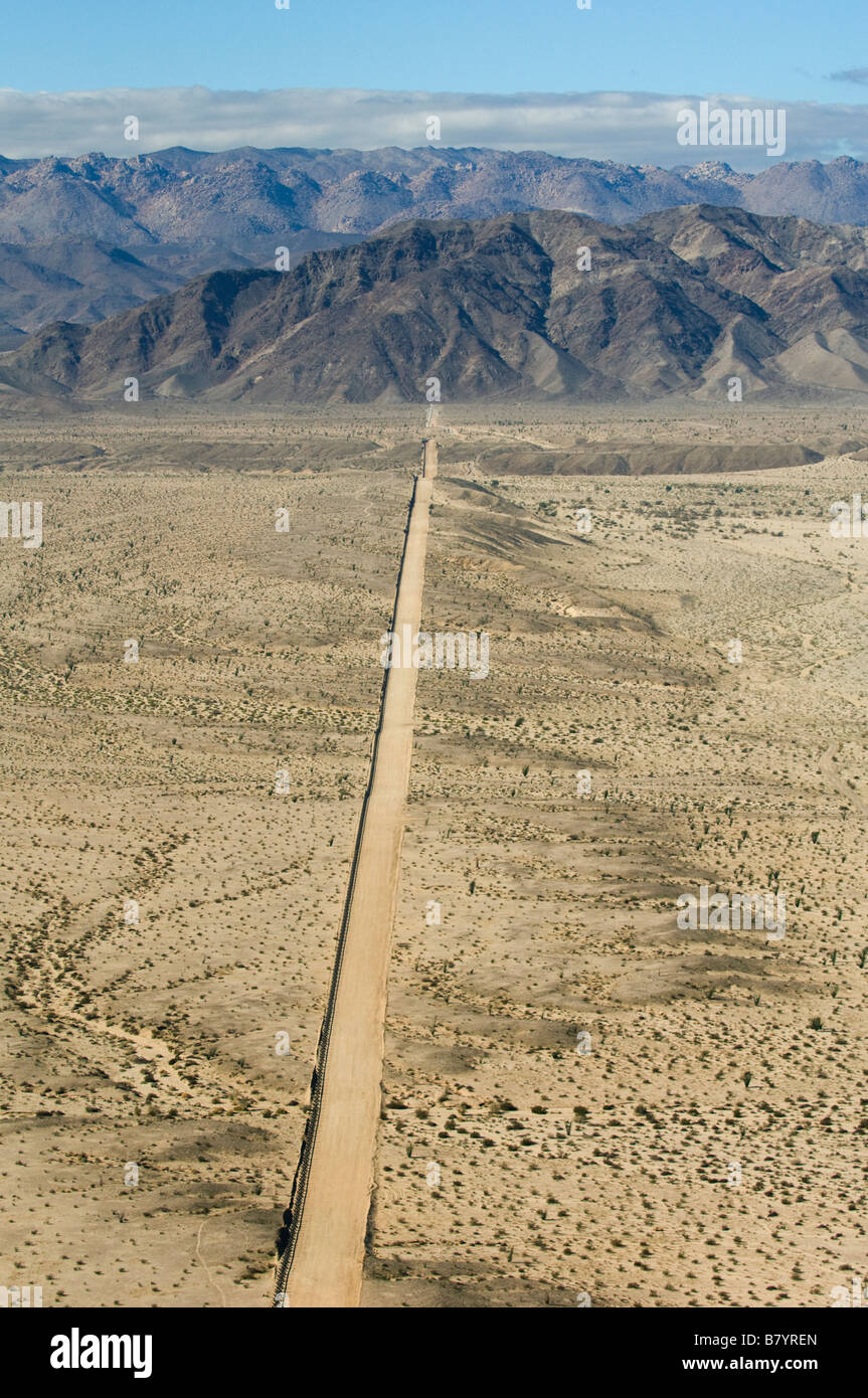 US Mexico Border Fence and access road, Yuha Desert, Imperial Valley, California, Looking West,  AERIAL - Stock Image