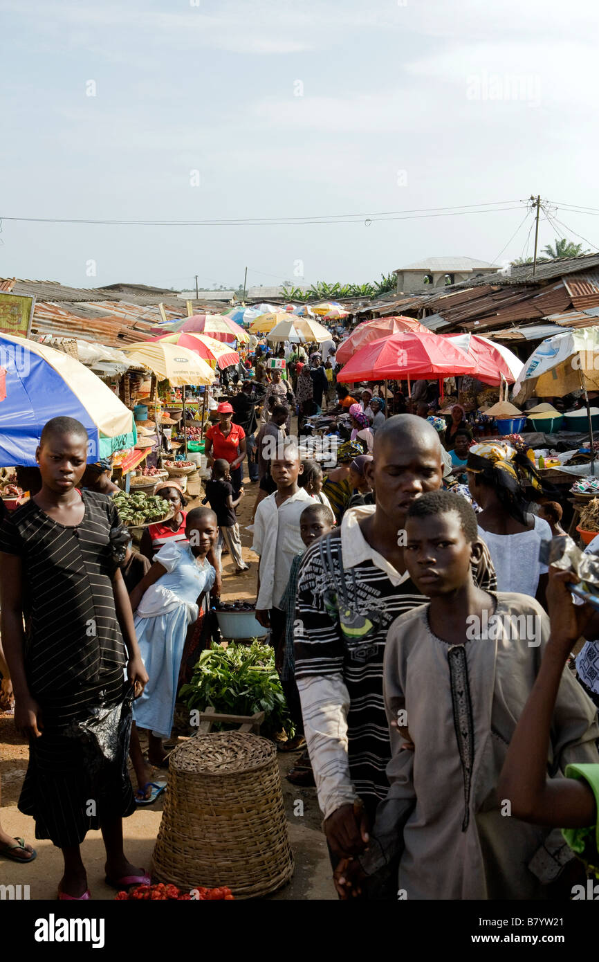 A crown of local shoppers at Poka market in Nigeria look strangely at the white man taking their photo - Stock Image