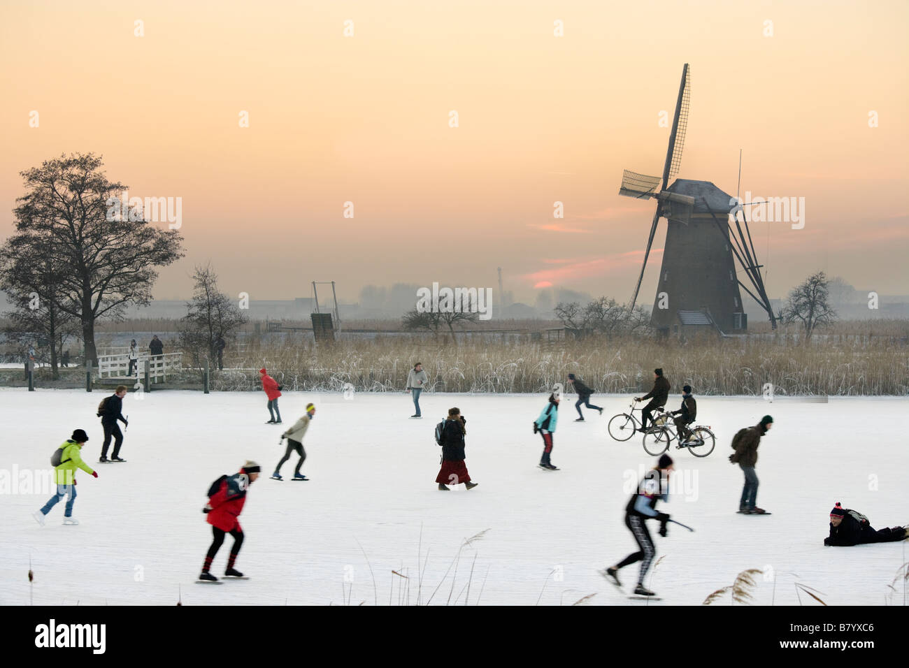 Ice skaters and even cyclists on natural ice in front of a windmill at Kinderdijk Holland, The Netherlands. At sunset. - Stock Image