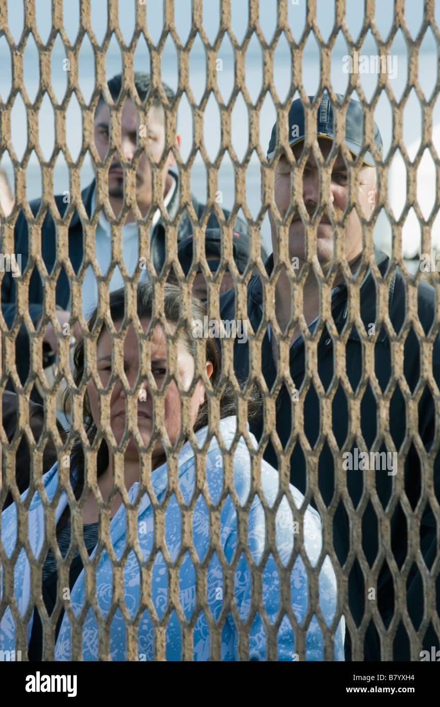 Mexicans behind US-Mexico Border fence, Tijuana Mexico - Stock Image