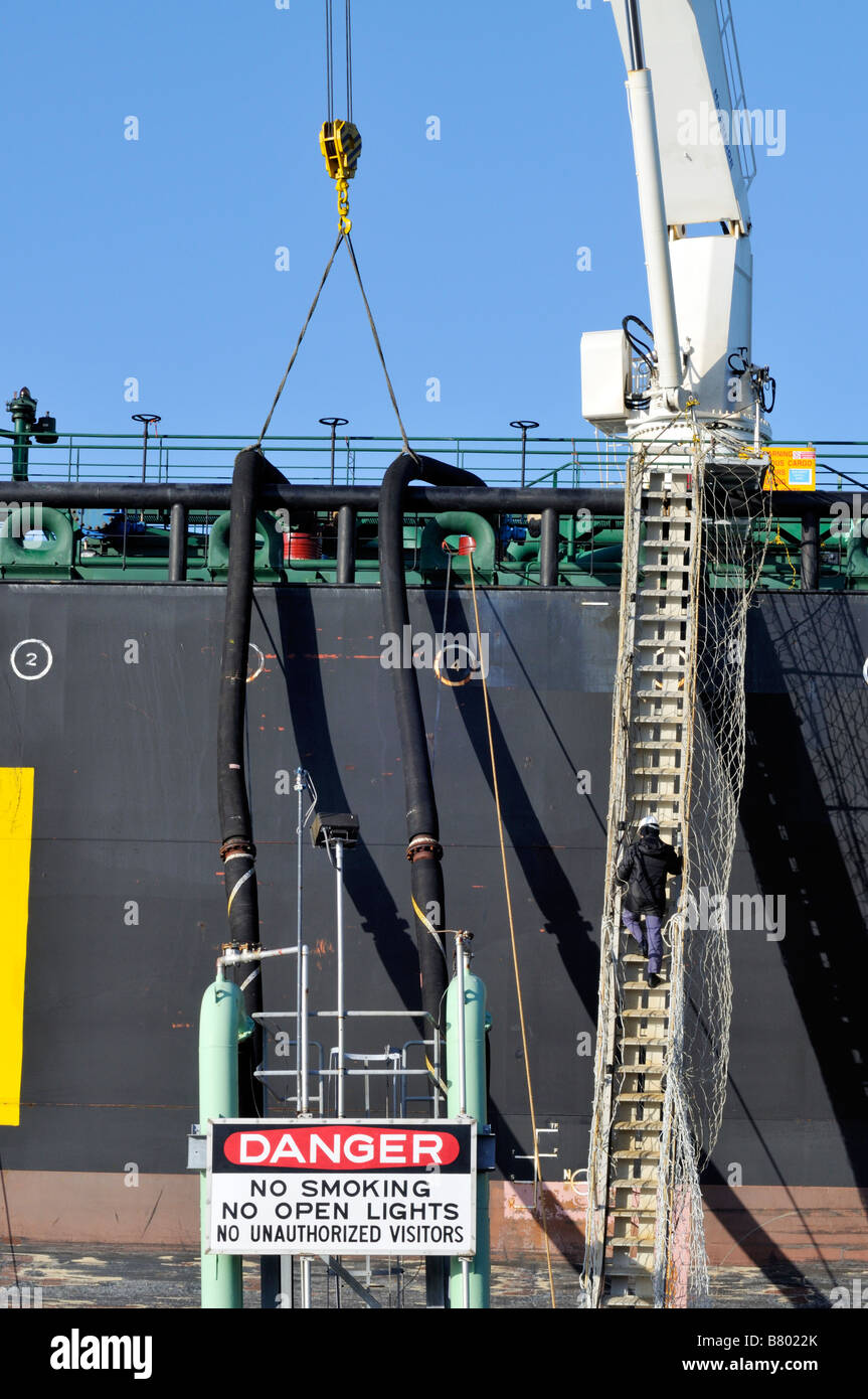 Offloading fuel from a tanker ship showing 2 hoses connected from ship to shore with single man climbing up long - Stock Image