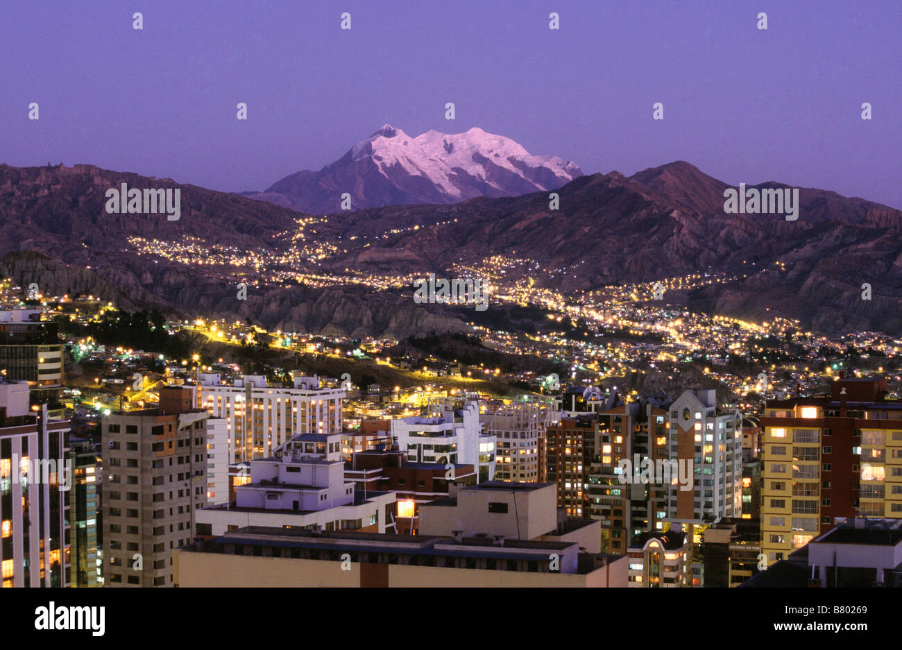 Central La Paz, lights of Zona Sur in distance and Mt Illimani at sunset, Bolivia - Stock Image