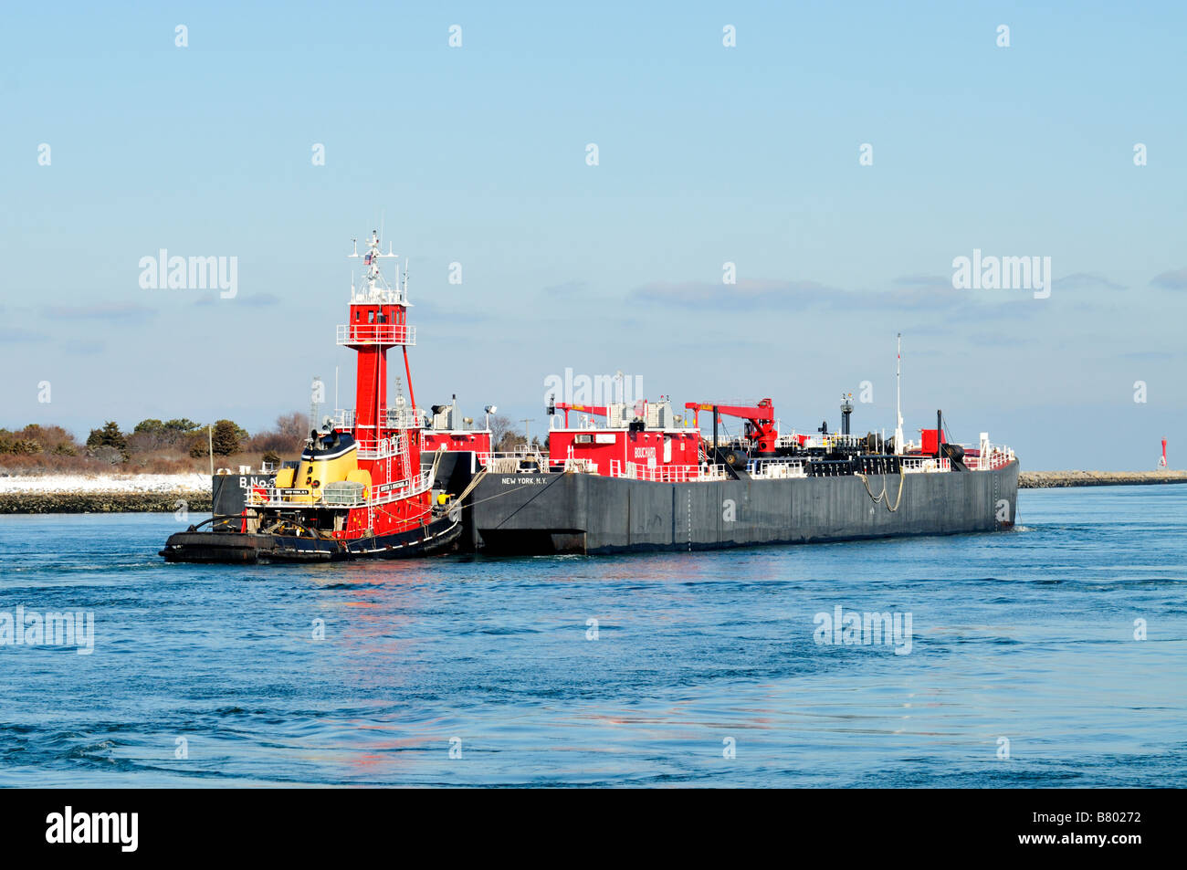 Red tugboat and barge heading out to sea on clear winter day