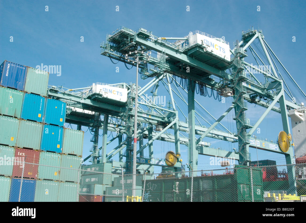 Cargo carriers loading and unloading a group of cargo containers - Stock Image