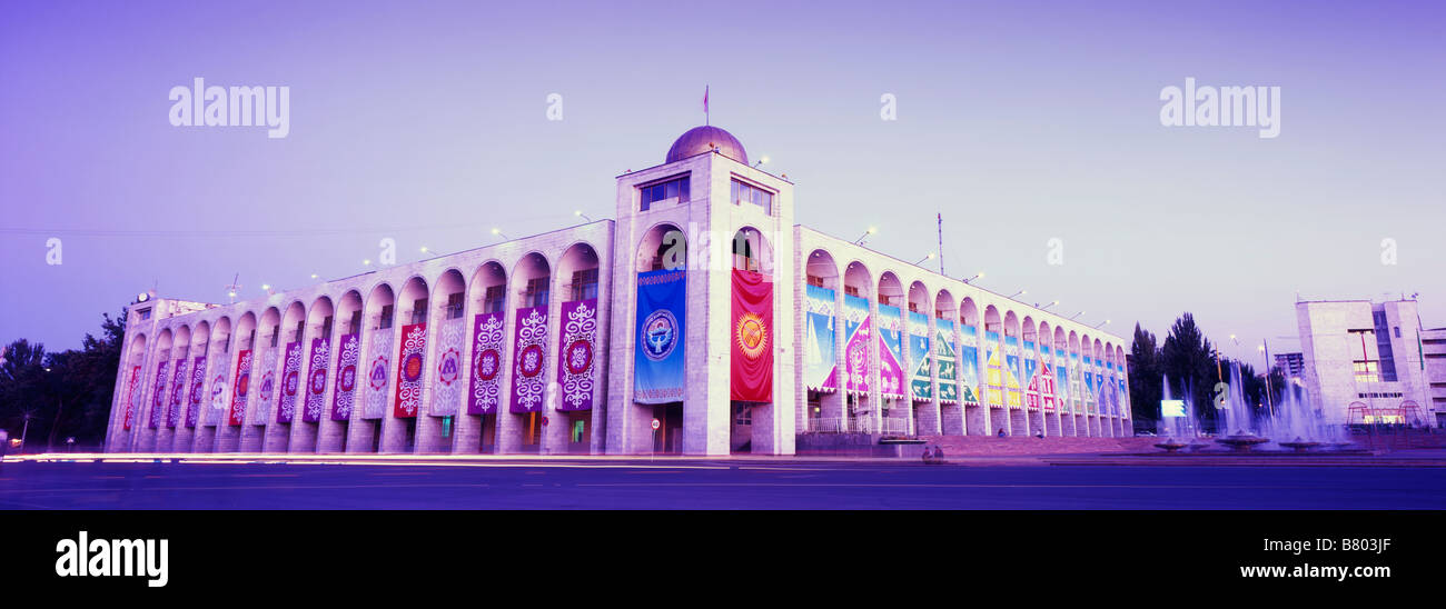 Panoramic evening shot of a Soviet-era building decorated with colourful Kygyz banners on Bishkek's central - Stock Image