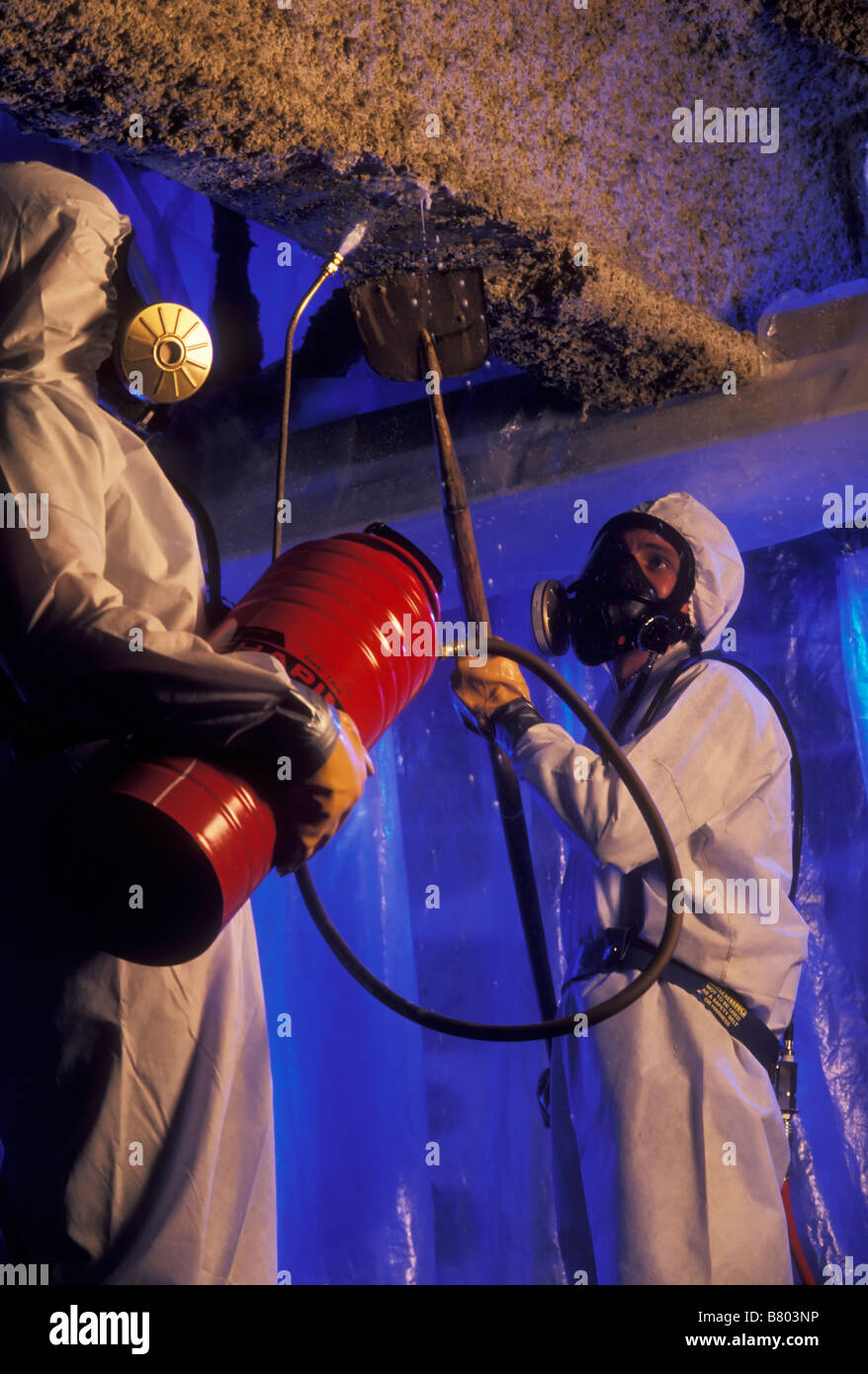 Asbestos insulation being removed by worker. Canada. - Stock Image