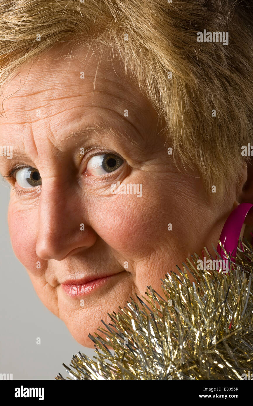 Portrait of a middle aged woman wearing tinsel - Stock Image