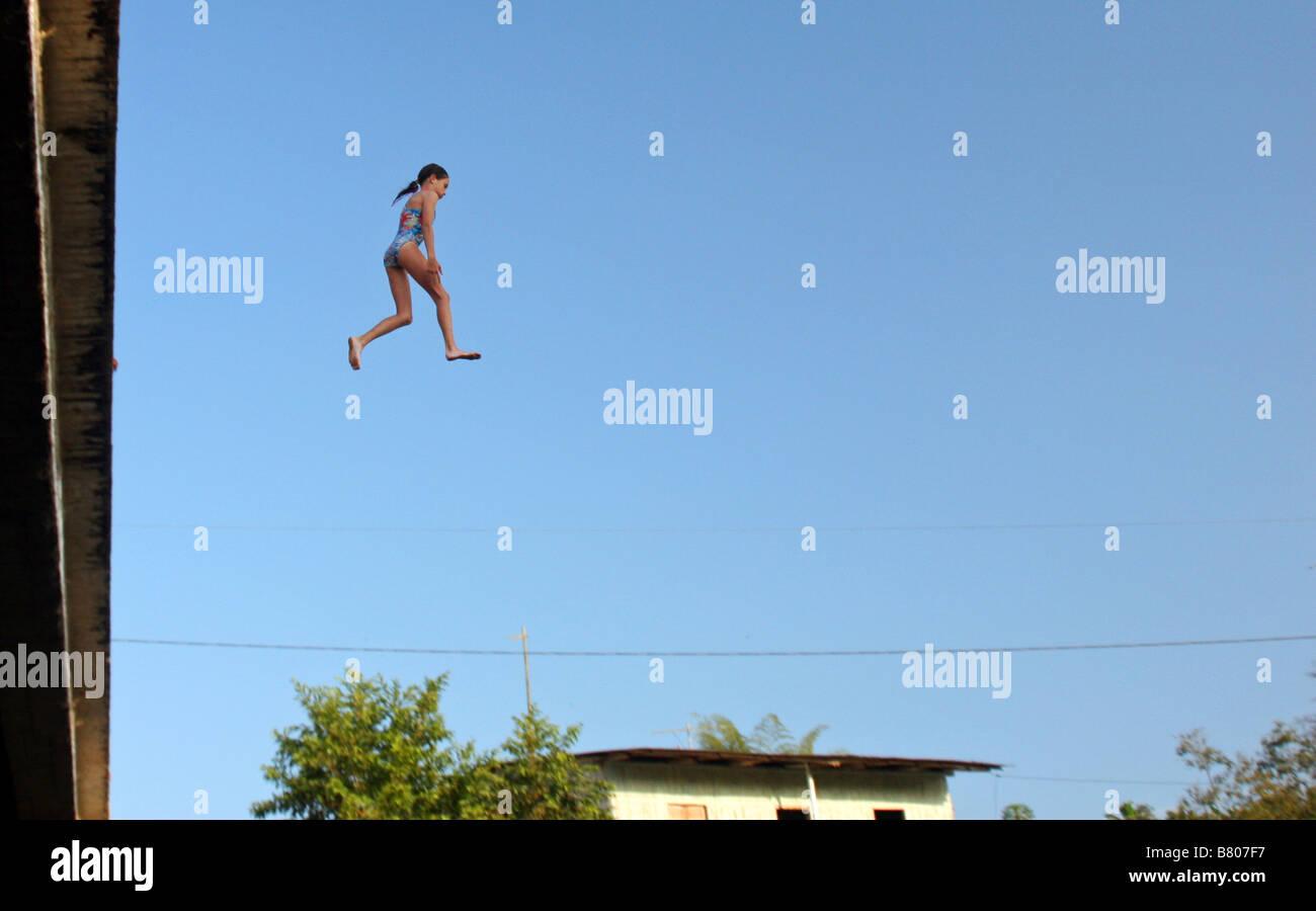 Girl jumping from high bridge ouside Quito Ecuador South America - Stock Image