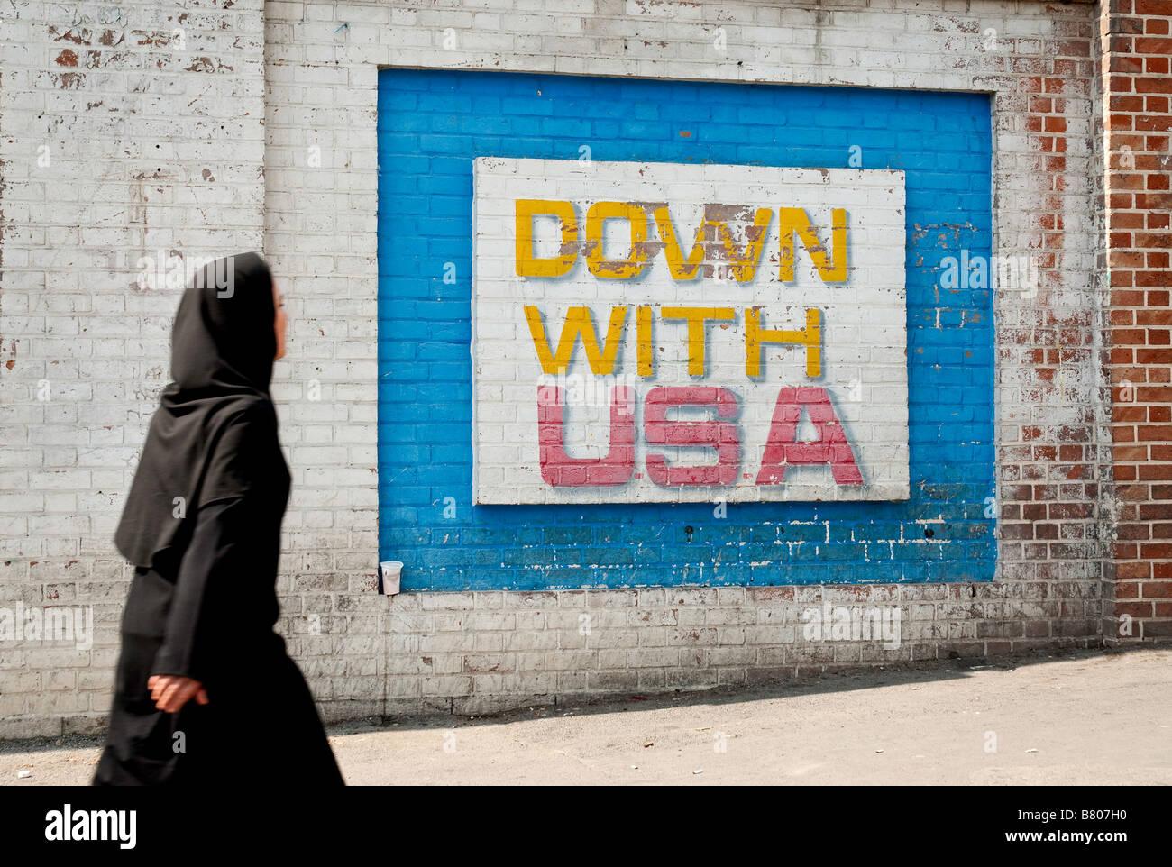 tehran black cloak wearing muslim woman walking past anti american mural outside old american embassy in teheran - Stock Image