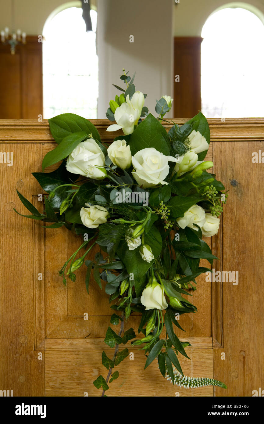 rose wedding flower arrangement over end of a church pew - Stock Image