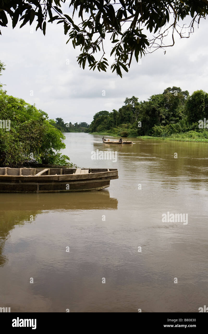 Two flat-bottomed boats that have been tied together and manned by two men transport sand along the Leeki Lagoon - Stock Image