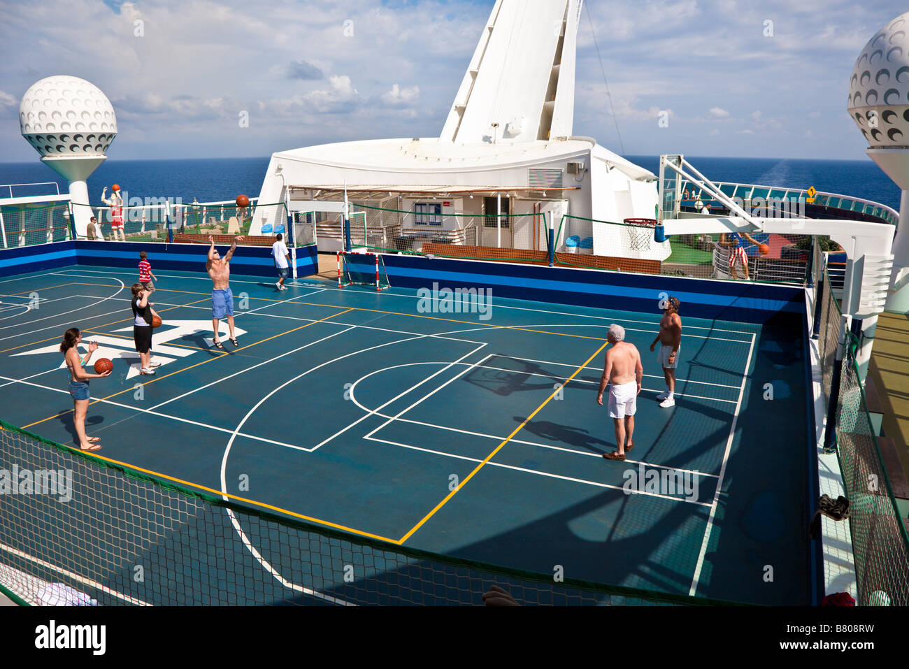 Cruise guests play basketball on sports deck of Royal Caribbean's Navigator of the Seas cruise ship - Stock Image