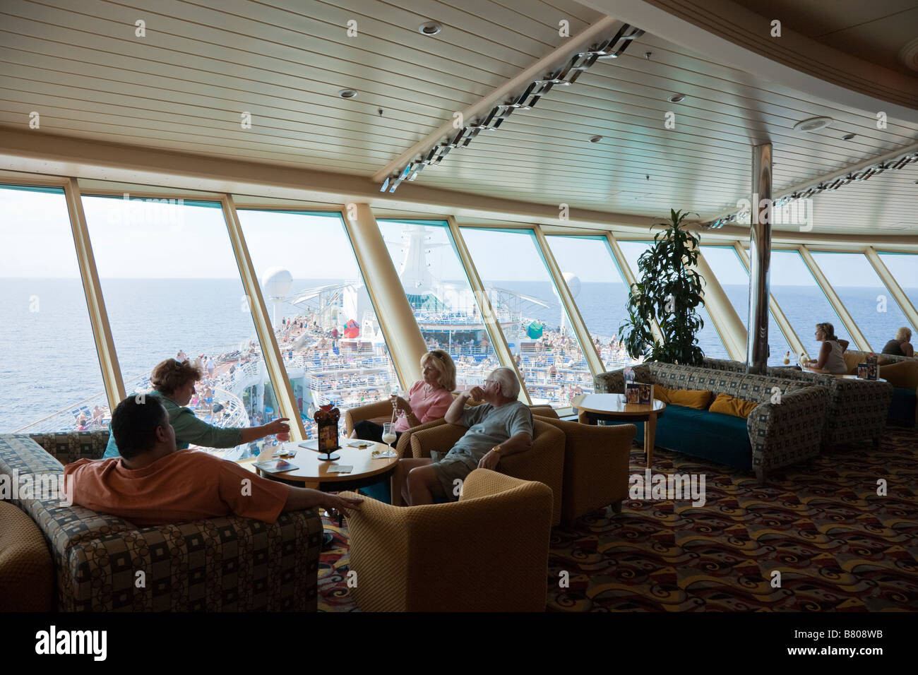 Cruise guests in elevated bar overlooking deck of Royal Caribbean Navigator of the Seas cruise ship - Stock Image