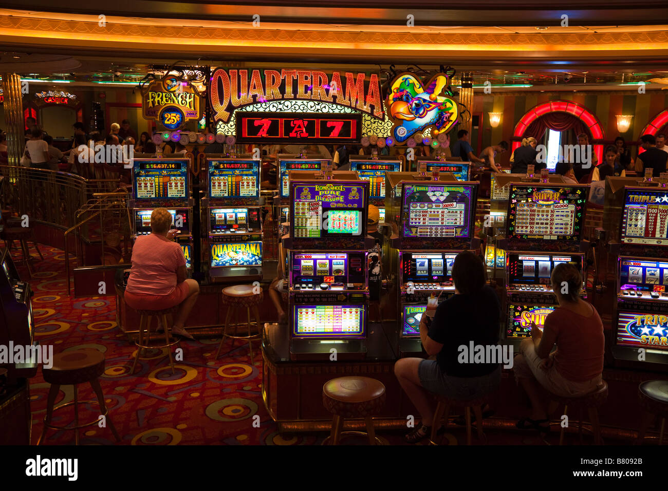 People playing slot machines in casino on Royal Caribbean Navigator of the Seas cruise ship - Stock Image