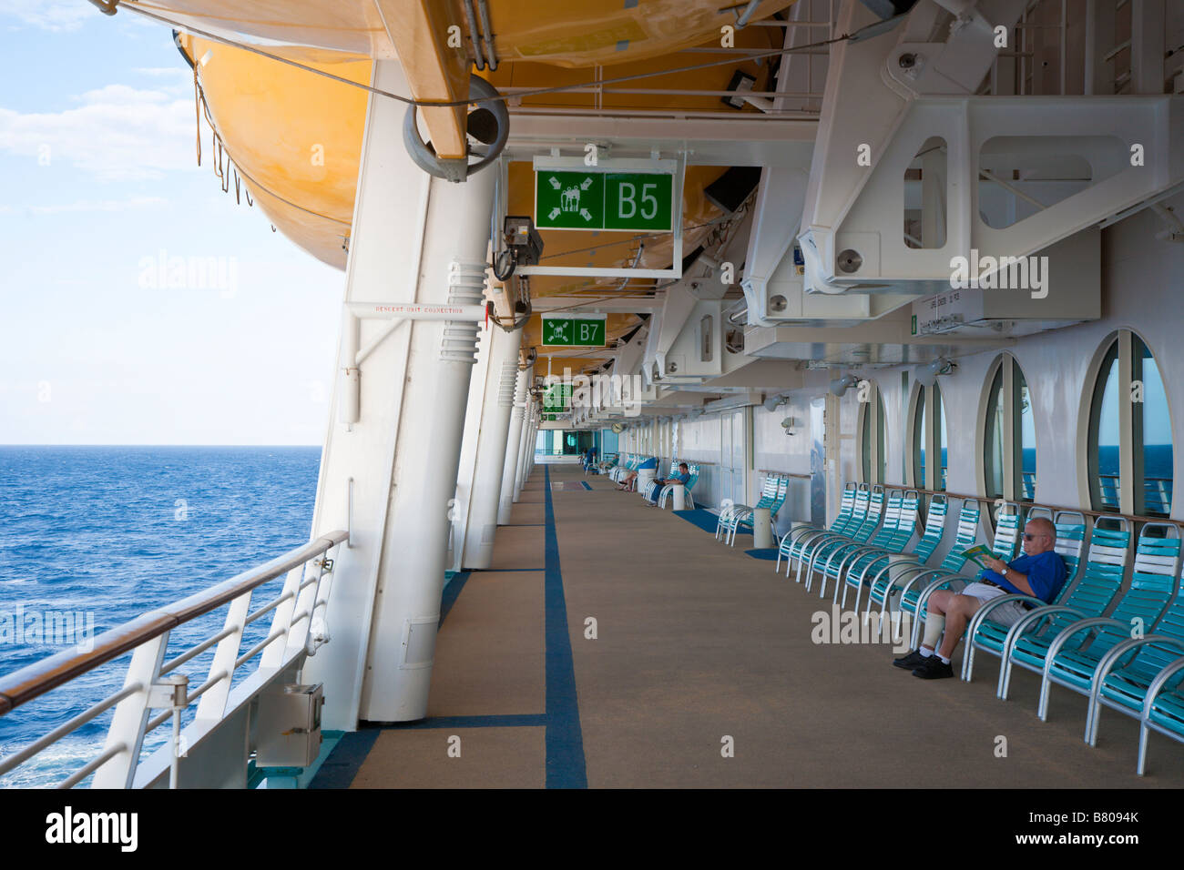 Man sits alone on deck of Royal Caribbean Navigator of the Seas in the shade of overhead lifeboats - Stock Image