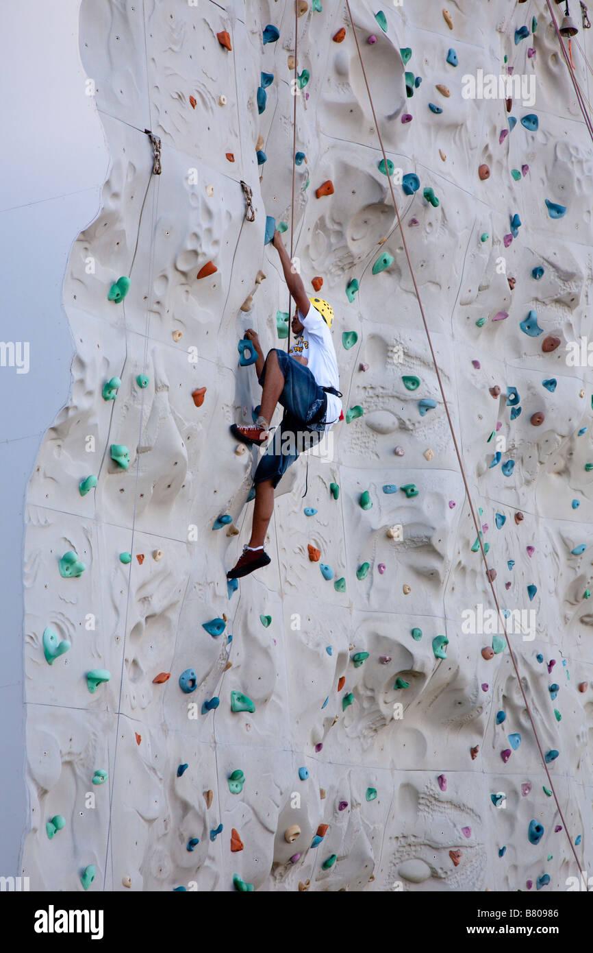 Teenage boy climbing artificial rock wall onboard Royal Caribbean Navigator of the Seas cruise ship - Stock Image