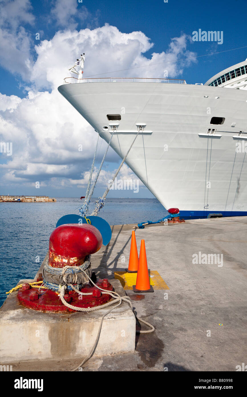 Royal Caribbean Navigator of the Seas cruise ship tied to bright red bollard on the dock in Cozumel, Mexico - Stock Image