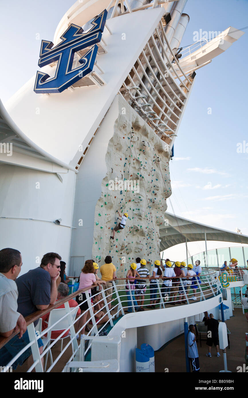 Teenage boy climbing artificial rock wall onboard Royal Caribbean Navigator of the Seas cruise ship - Stock Image