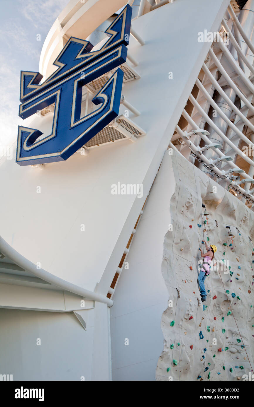 Teenage girl climbing artificial rock wall onboard Royal Caribbean Navigator of the Seas cruise ship - Stock Image