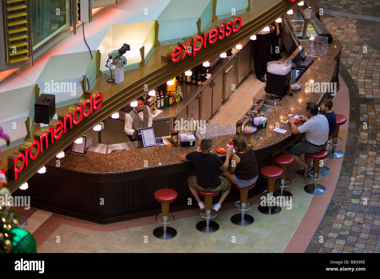 Cruise passengers sit at Expresso bar on Royal Promenade deck of Royal Caribbean Navigator of the Seas cruise ship - Stock Image