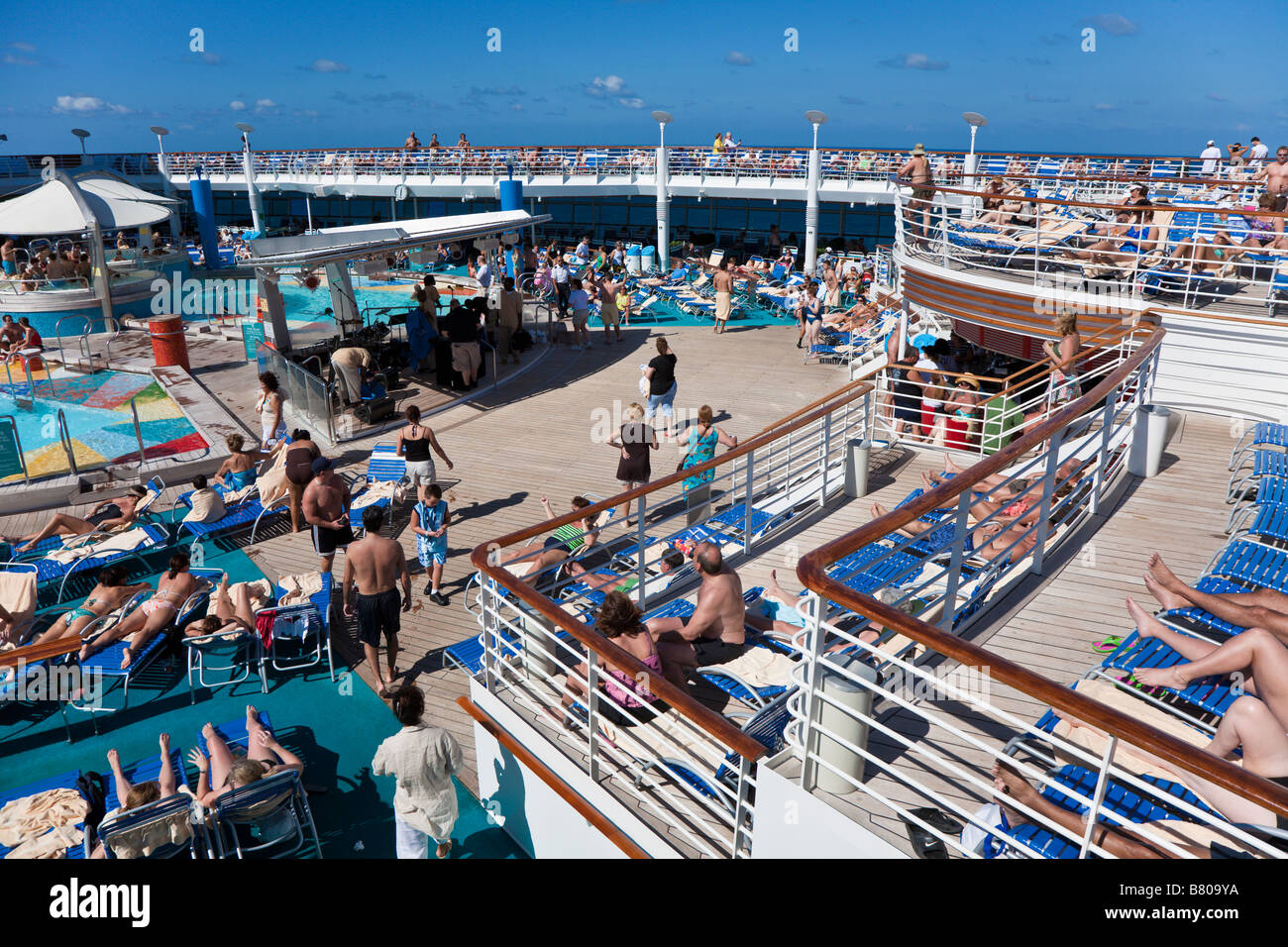 Cruise ship passengers lounging on the sun deck around the pool on Royal Caribbean Navigator of the Seas - Stock Image