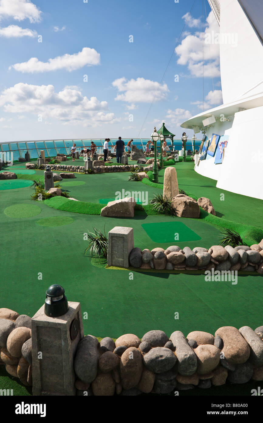 Crusie guests play miniature golf on the deck of the Royal Caribbean Navigator of the Seas cruise ship - Stock Image