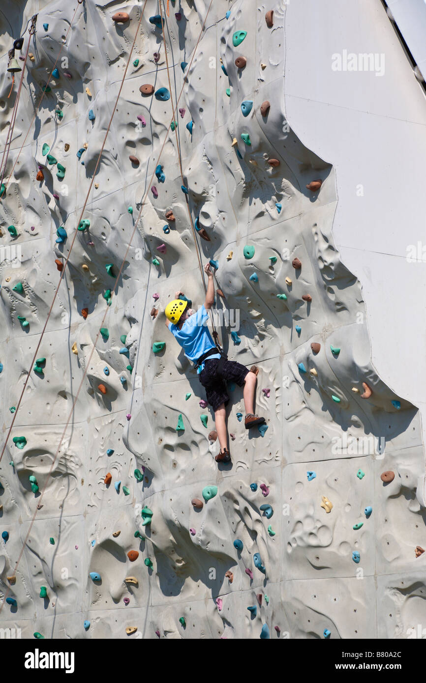 Cruise passenger climbing artificial rock wall onboard Royal Caribbean Navigator of the Seas cruise ship - Stock Image