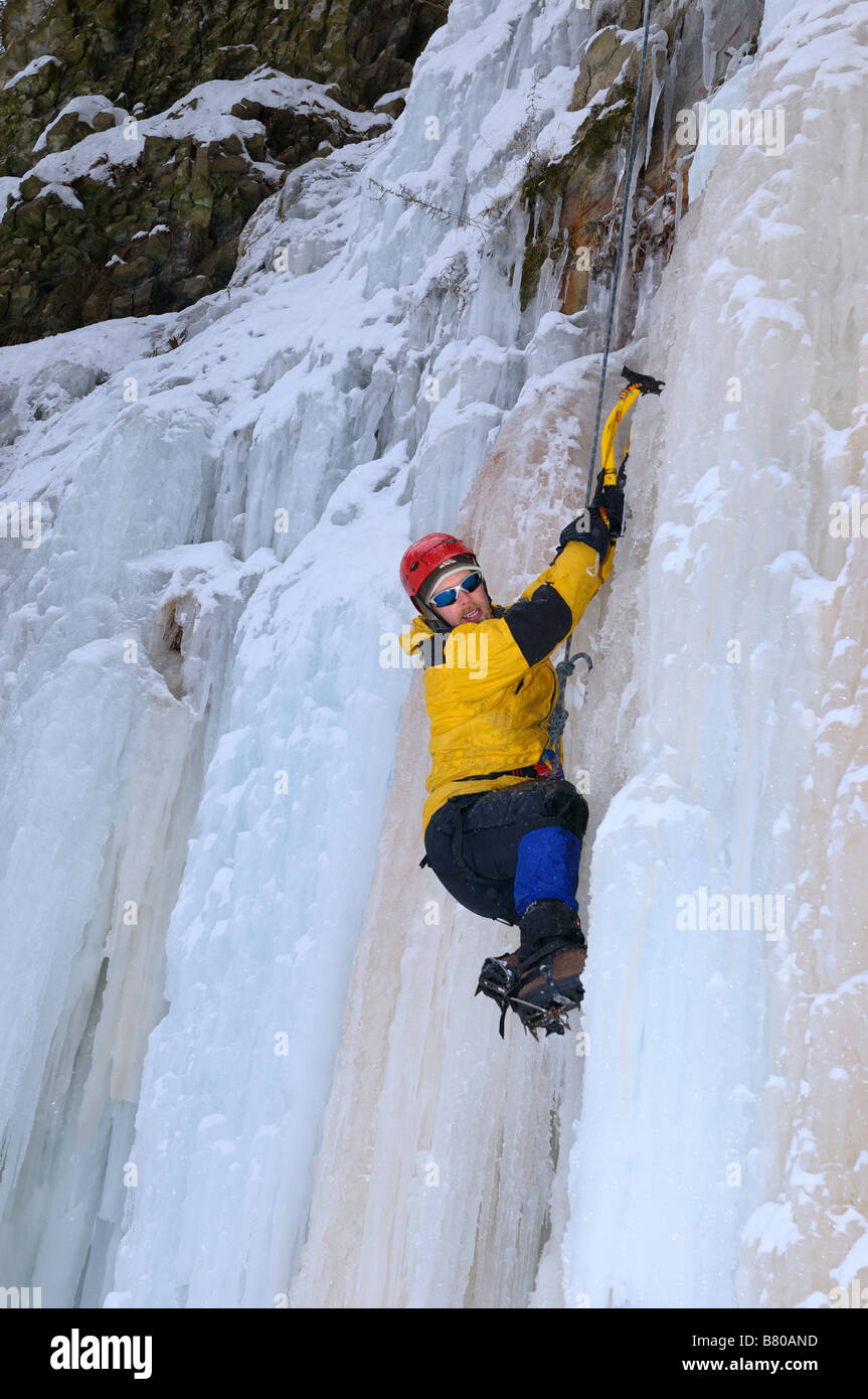 Ice climber on belay hanging on and looking for foothold on a wall of ice at Tiffany Falls Ontario - Stock Image