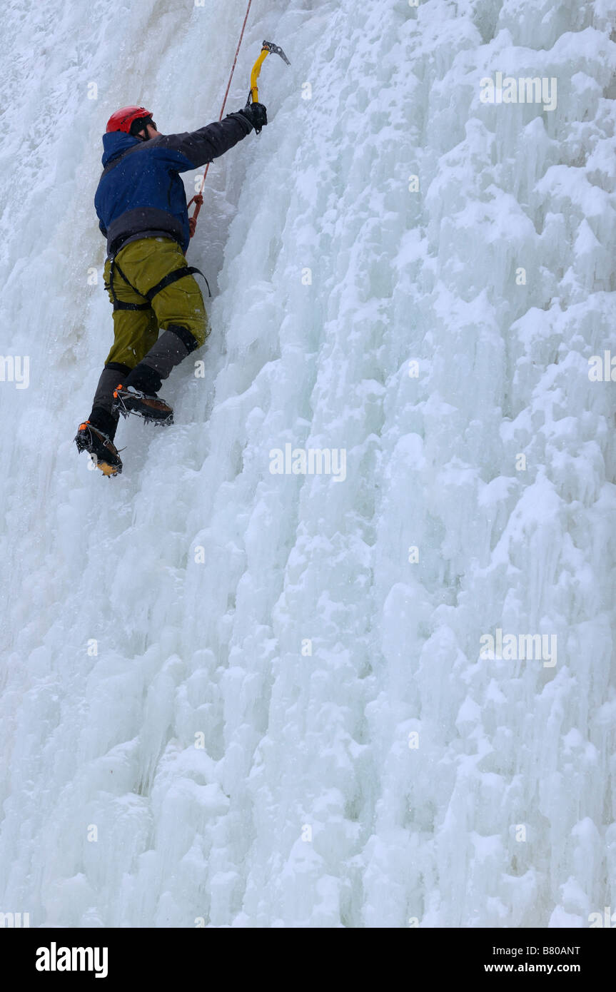 Single ice climber front pointing up a wall of ice on belay at Tiffany Falls Ontario - Stock Image
