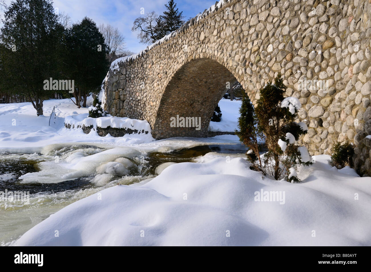 Spencer Creek running under a stone bridge at Webster Falls Conservation Area Park in winter - Stock Image
