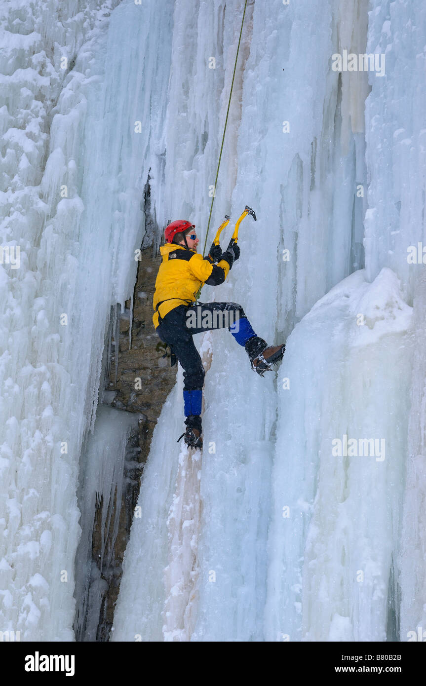 Ice climber front pointing up a steep icefall with top rope belay at Tiffany Falls Ontario - Stock Image