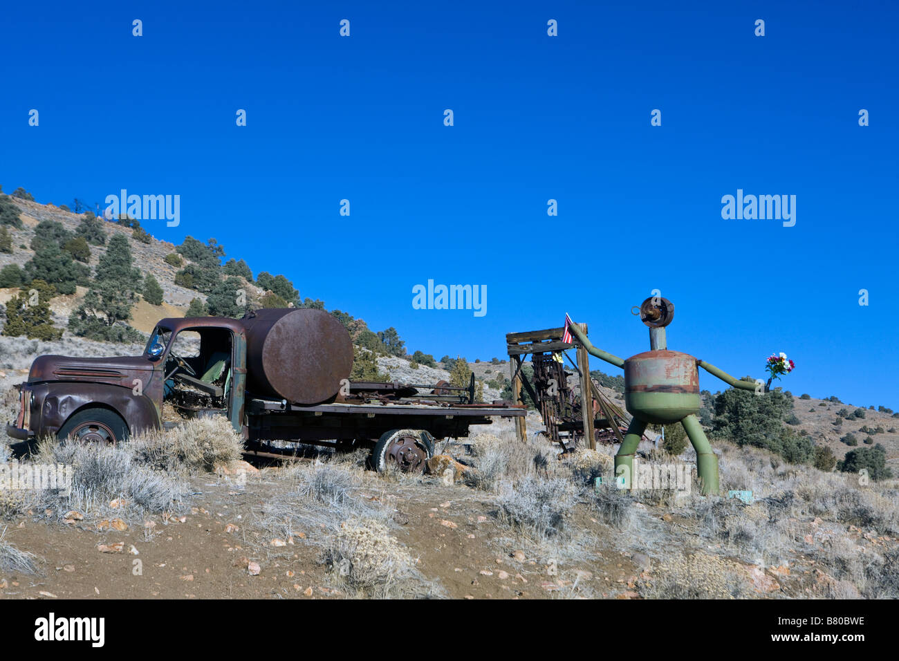 A rusted tanker truck and sculptures made from automobile parts along a hill side south of Virginia City Nevada Stock Photo