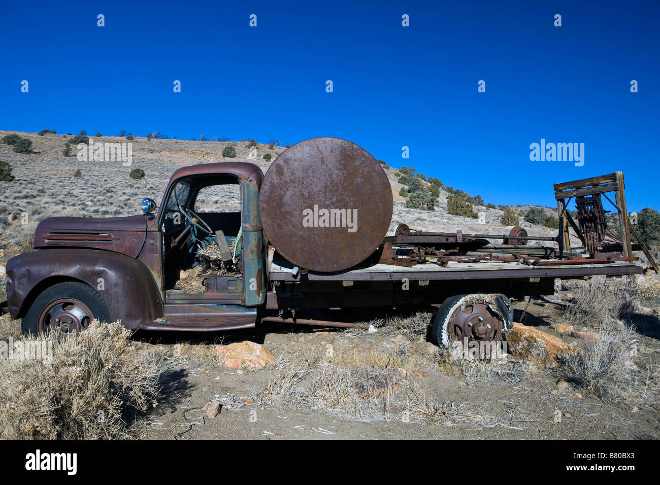 An old rusty truck with a tank in it s bed sits along a hill side south of Virginia City Nevada Stock Photo