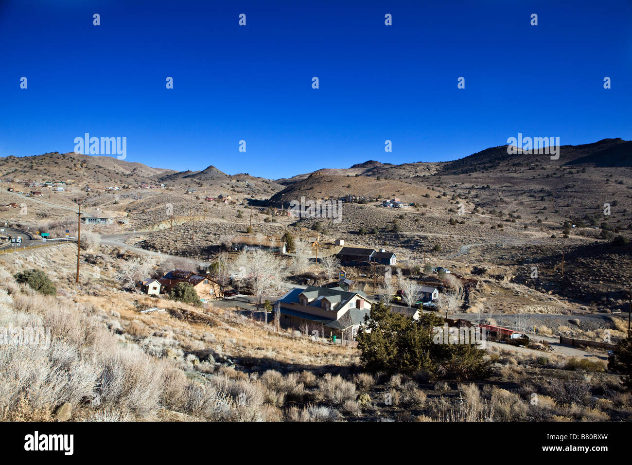 The town of Silver City Nevada with houses and buildings nestled between rolling hills south of Virginia City NV - Stock Image