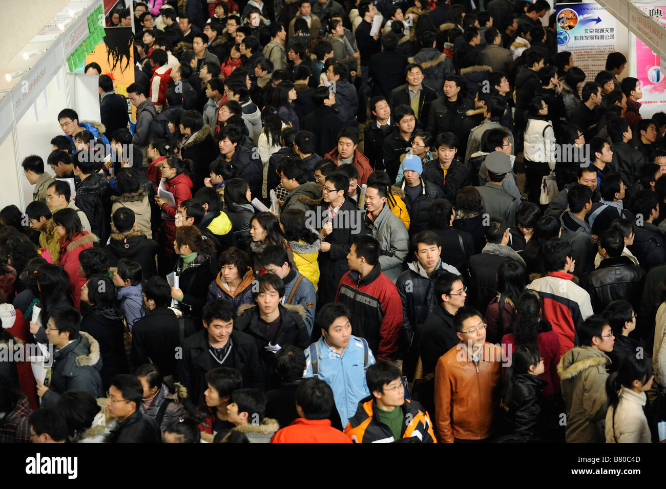 Job seekers crowd booths at a job fair in Beijing on February 8, 2009. - Stock Image