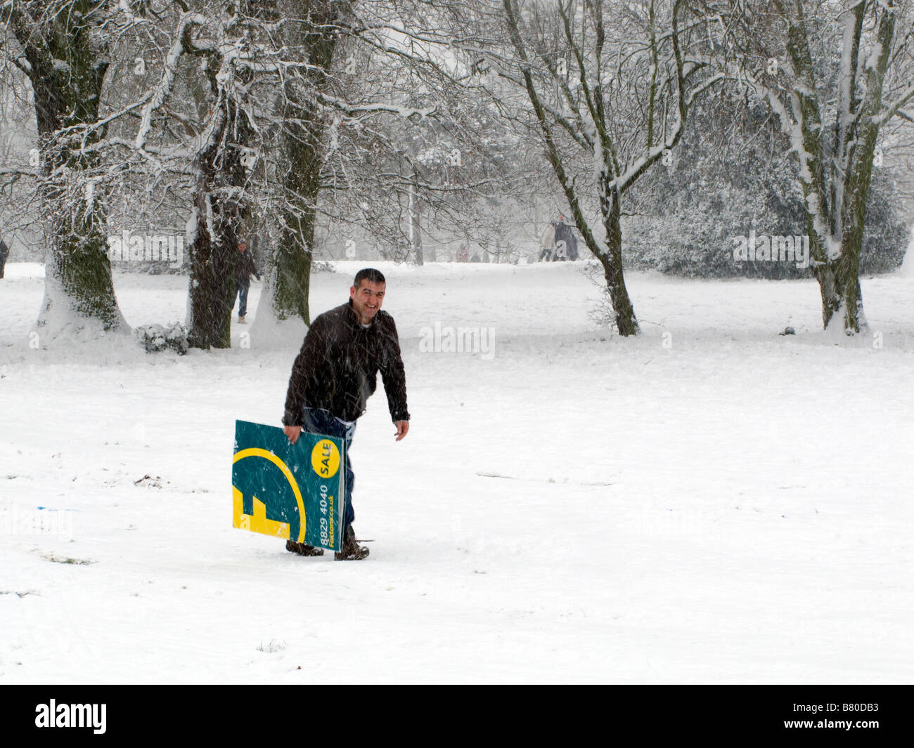Foxtons estate agent sign carried by man to use as a sledge. - Stock Image