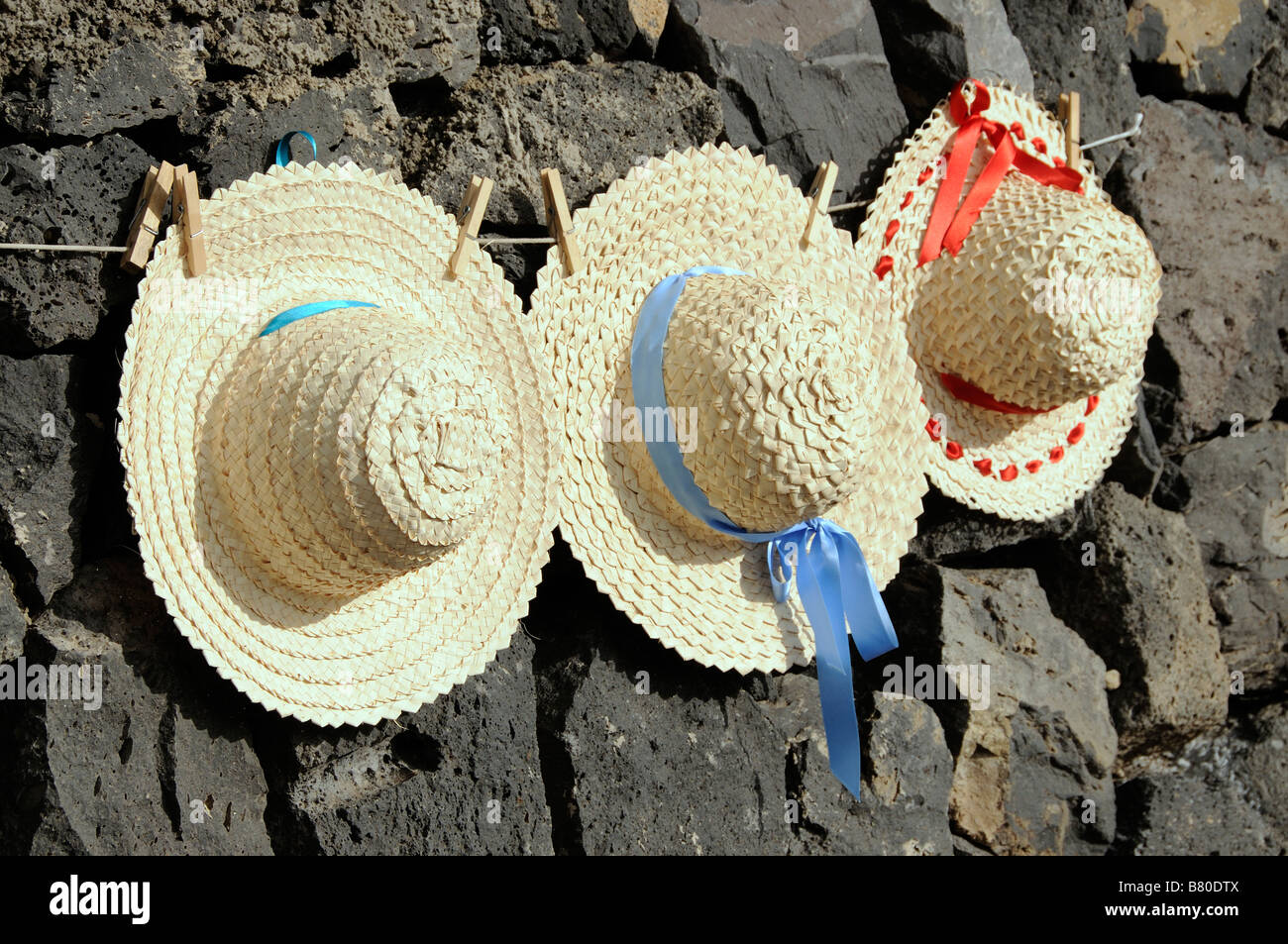 Straw hats handmade in the Canary Islands pegged on a line and on sale as souvenirs for the tourist trade. - Stock Image