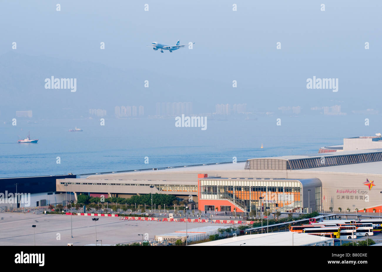 An airplane arrives at Hong Kong Chek Lap Kok Airport next to Asia World Expo in Hong Kong Stock Photo