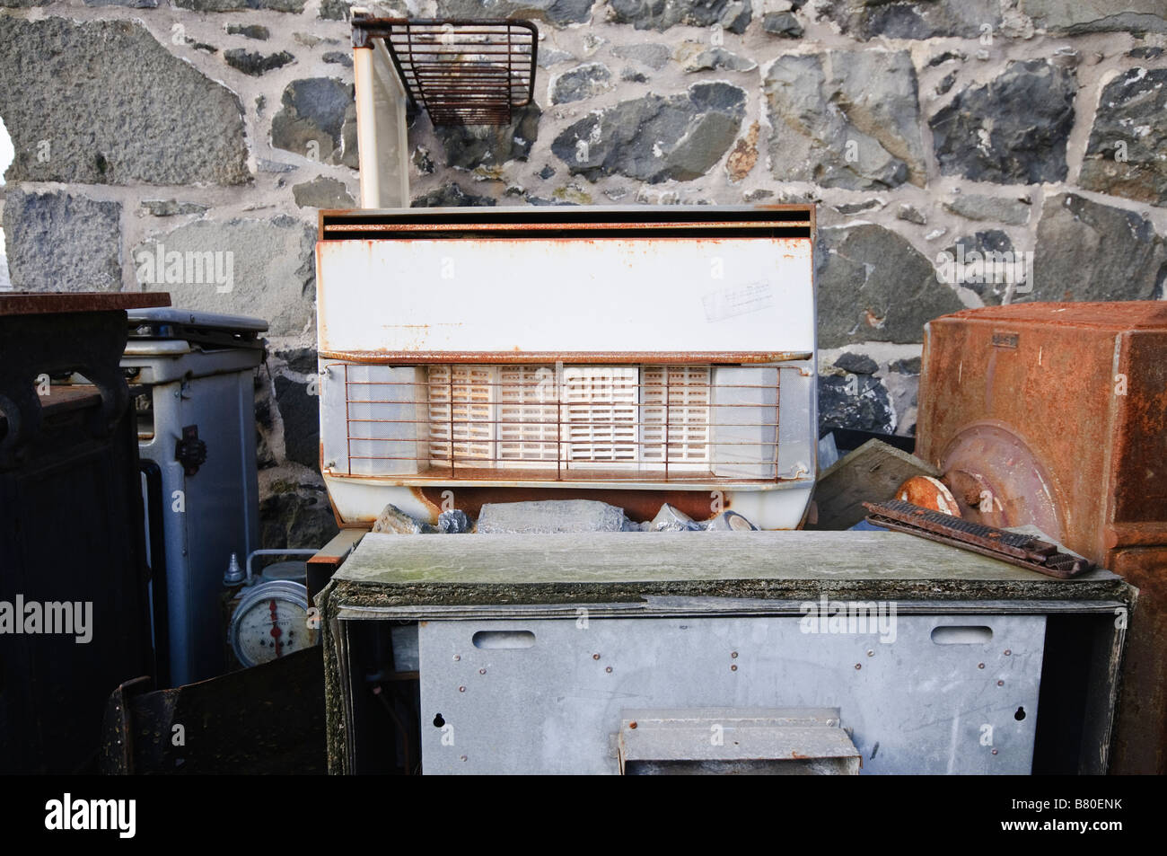Old gas appliances piled up outside for scrap metal - Stock Image