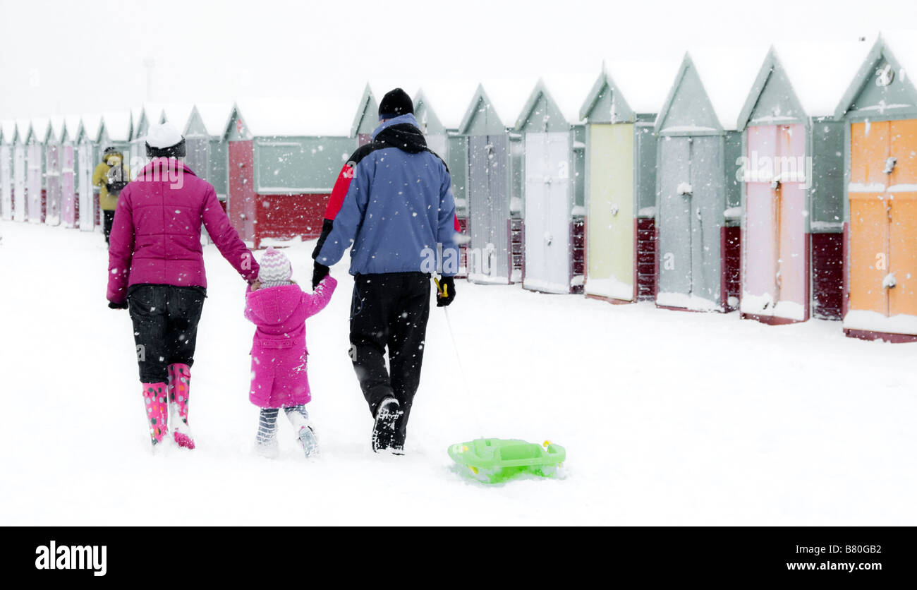 View of family group and snow covered beach huts on Brighton Beach, UK Stock Photo