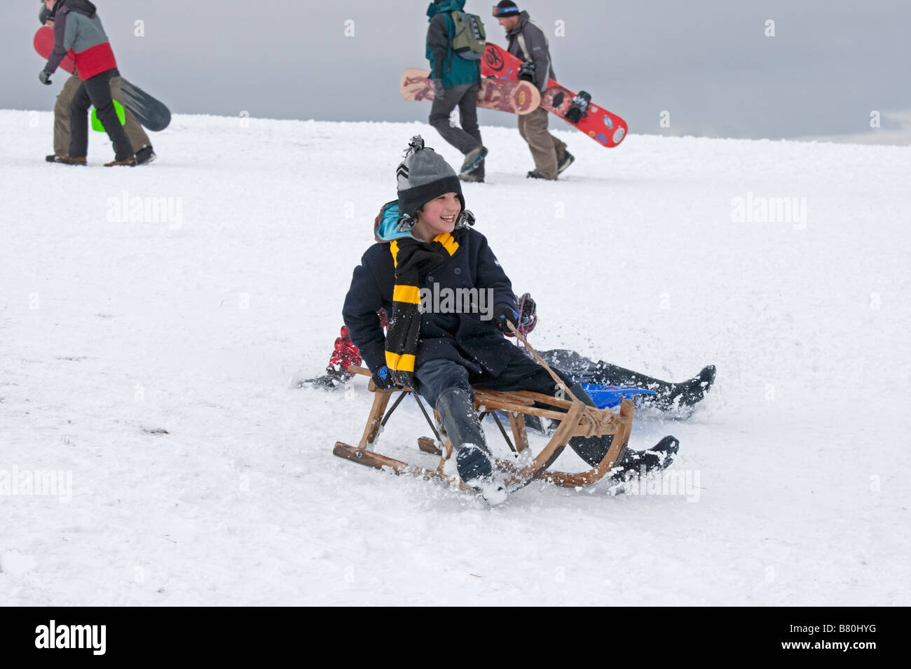 Child sledging in deep snow Cleeve Hill Cotswolds UK - Stock Image