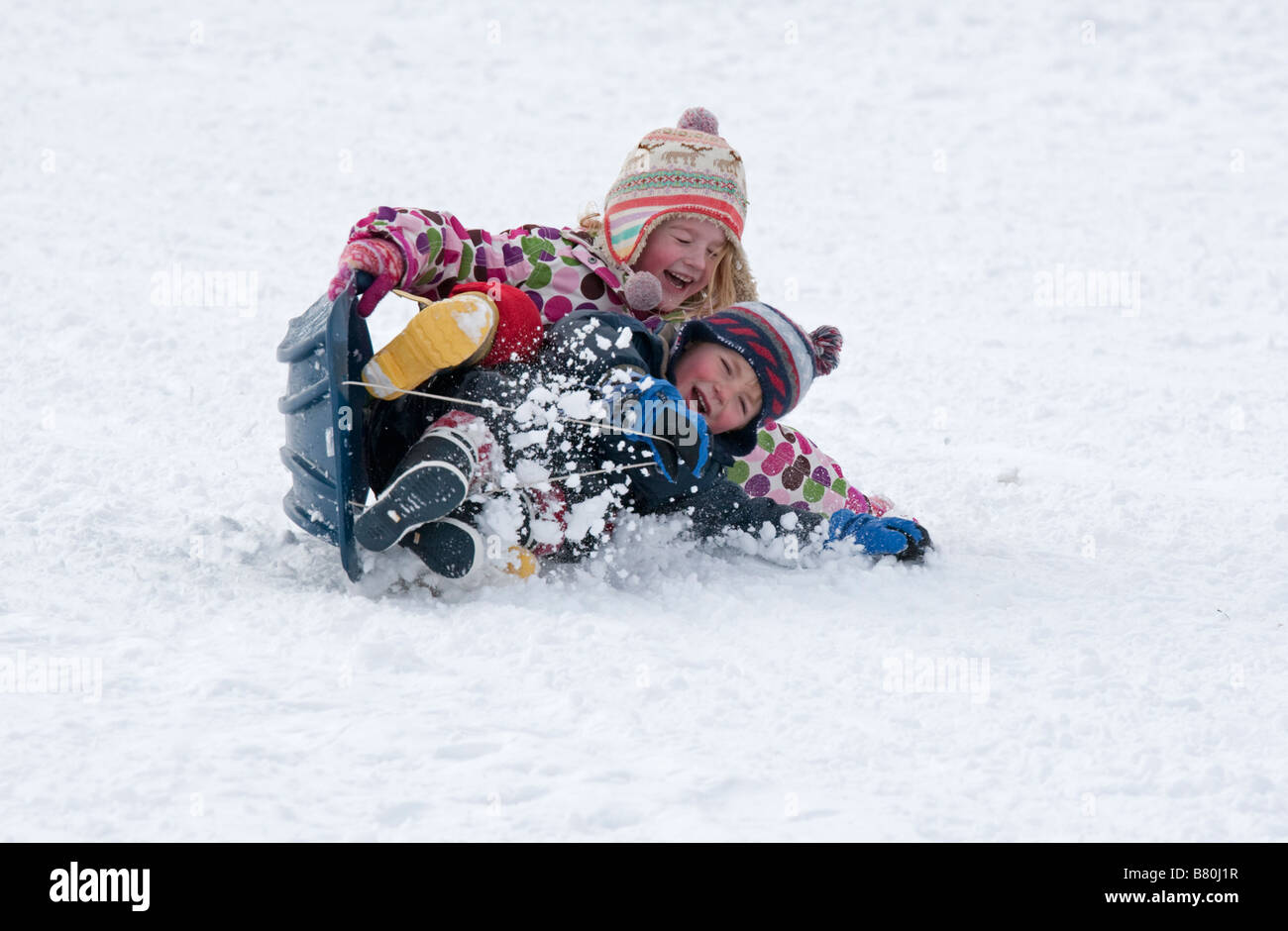 Young children falling off sledge in deep snow Cleeve Hill Cotswolds UK - Stock Image