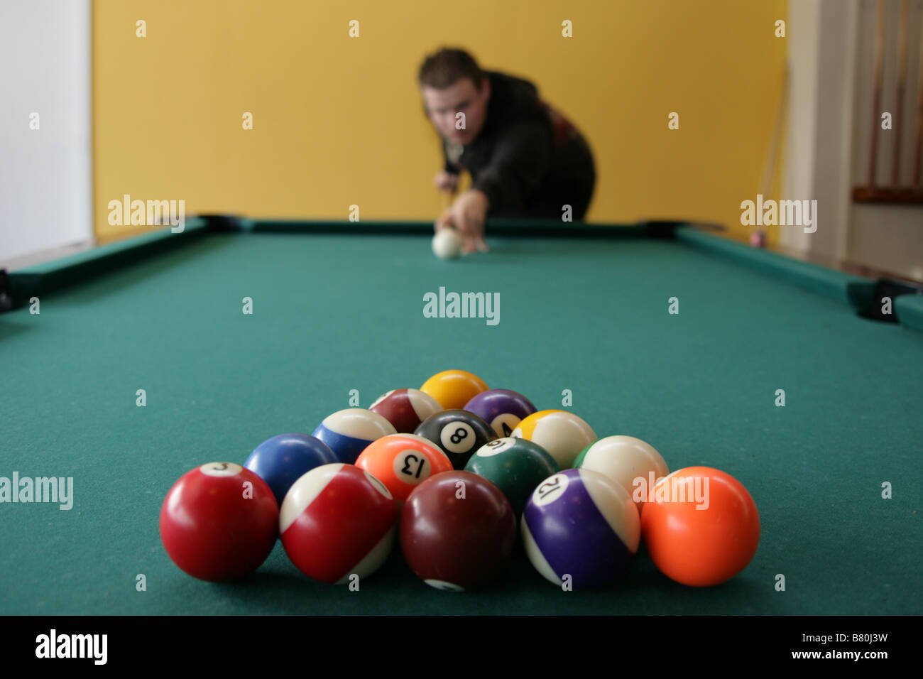 Young man aims cue stick at pool balls. - Stock Image