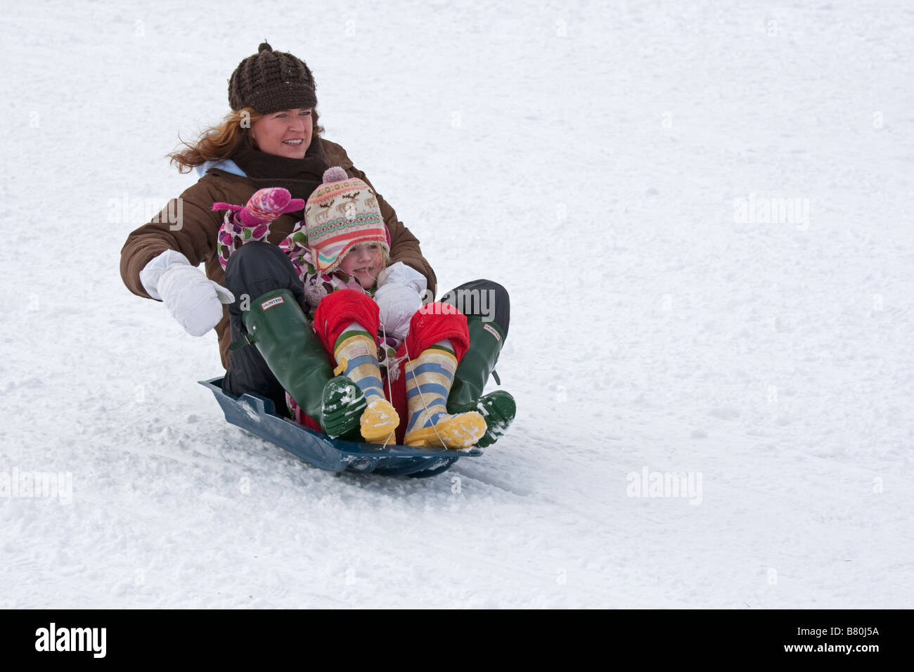 Mother and daughter sledging in deep snow Cleeve Hill Cotswolds UK - Stock Image
