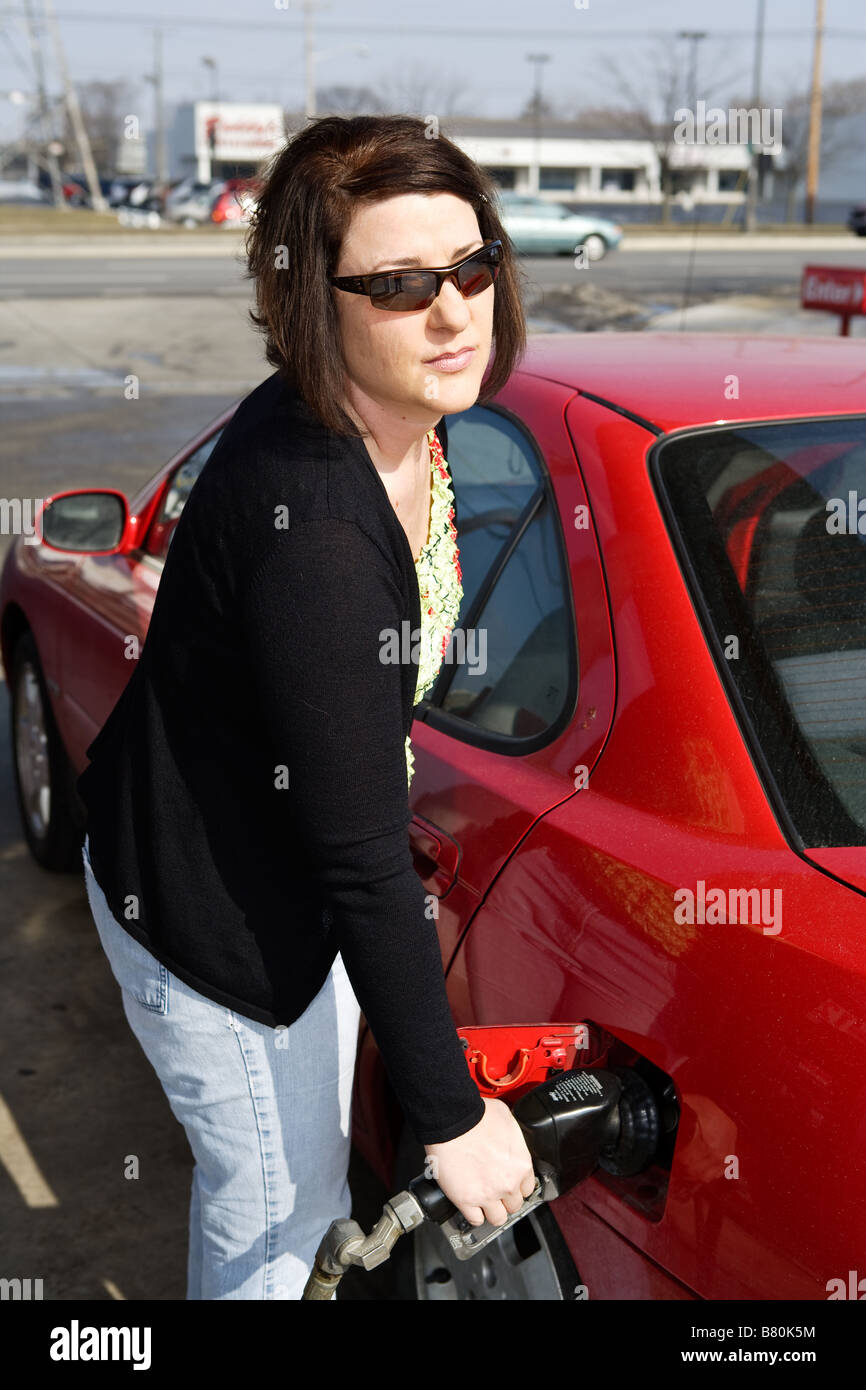 A woman pumping gasoline - Stock Image