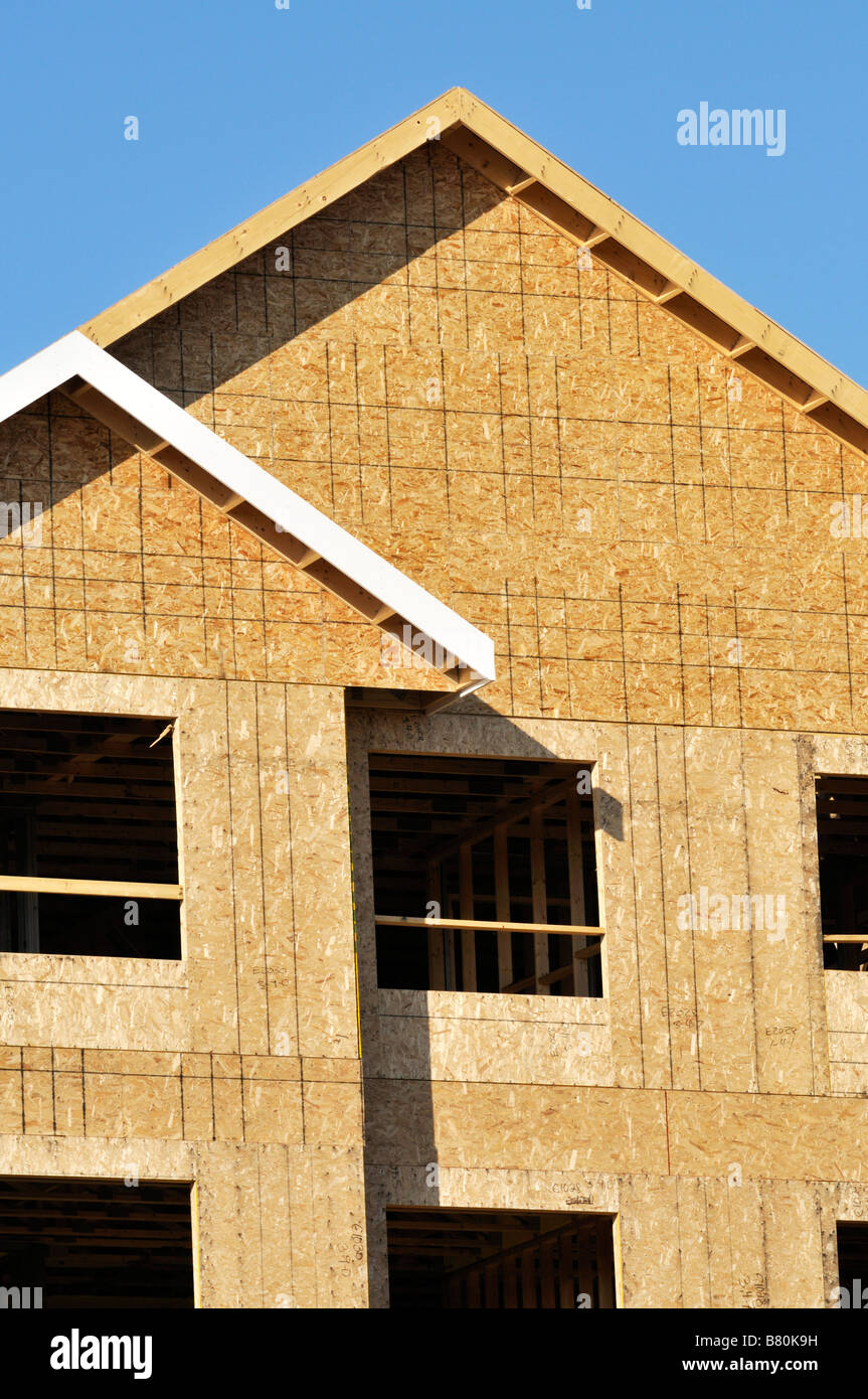 New Wood Frame Construction Roof Peak Of An Apartment Building With Window  Cutouts, Framing And Fiberboard.