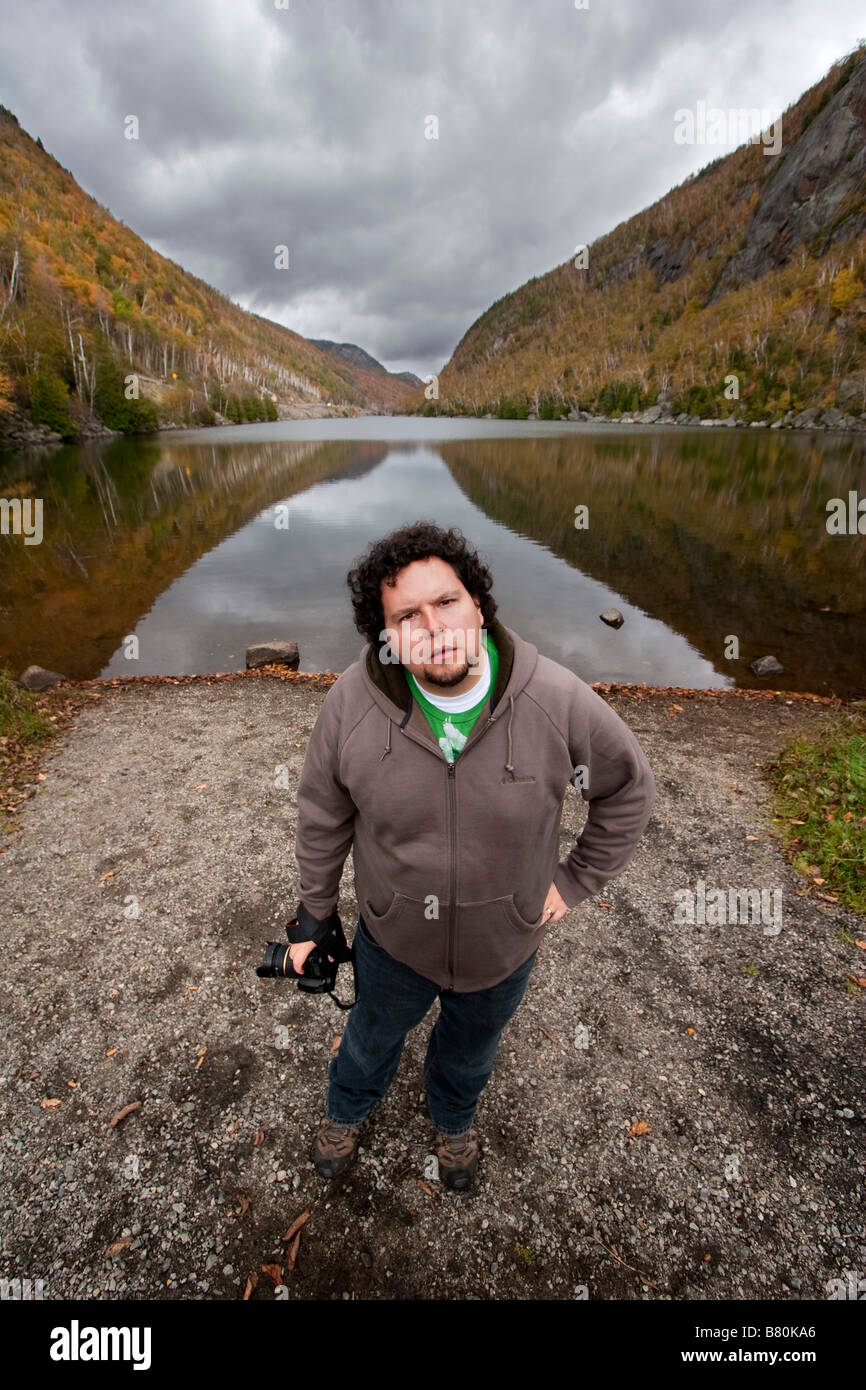 A man holding a camera standing in front of a lake in the Adirondacks of New York October 6 2008 MR YES - Stock Image