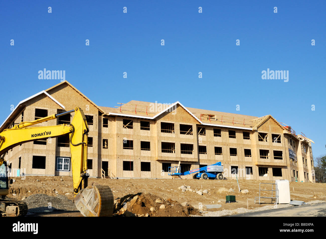 Apartment building construction site with the exterior wood frame and Komatsu excavator heavy equipment on site - Stock Image