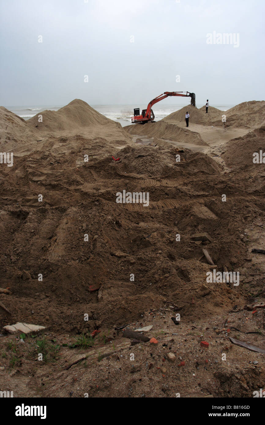 An excavator working on sandy beach in Terengganu, Malaysia Stock