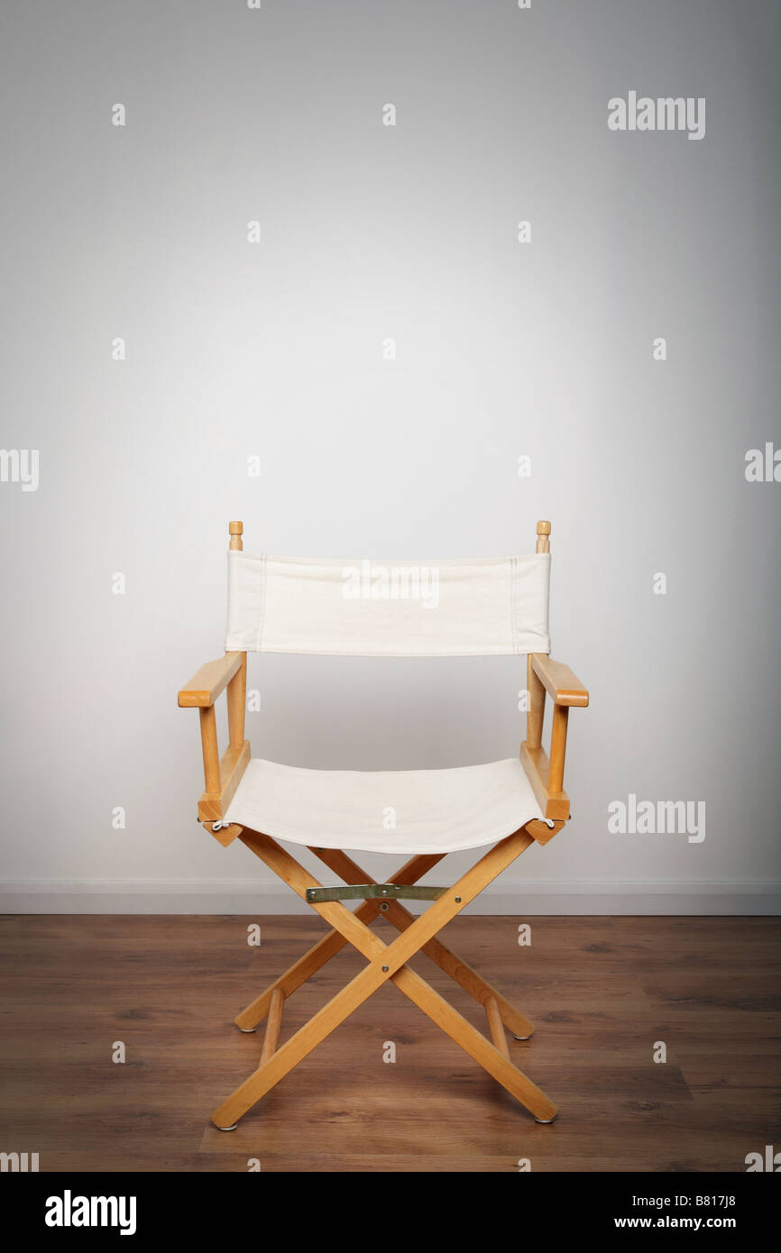 One chair on a wooden floor illuminated with a single light source - Stock Image